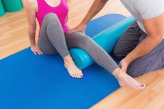 Trainer working with woman on exercise mat Stock Photography