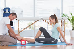 Trainer working with woman on exercise mat Royalty Free Stock Image