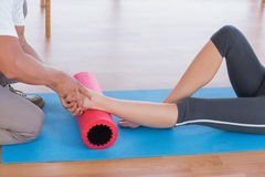 Trainer working with woman on exercise mat Stock Photos