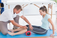 Trainer working with woman on exercise mat Royalty Free Stock Photos