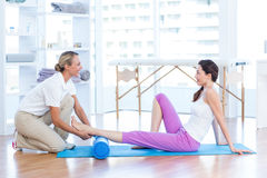 Trainer working with woman on exercise mat Royalty Free Stock Photography
