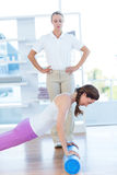 Trainer working with woman on exercise mat Stock Photo