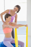 Trainer working with woman at fitness studio. Trainer working with young women at fitness studio Stock Photo