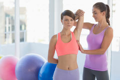 Trainer working with young woman. Trainer working with young women at fitness studio Stock Images
