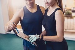 Trainer writes a fitness program training the girl stock photography