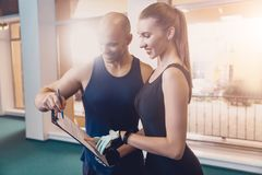 Trainer writes a fitness program training the girl stock image