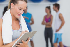 Trainer writing on clipboard with fitness class in background at gym Stock Image