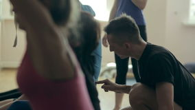 The trainer of yoga helps students. Group yoga class at the gym stock video footage