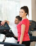 Trainer and young woman in fitness club Stock Photos