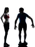 Trainermannfrau, die Hocken auf bosu Schattenbild ausübt Stockfotografie