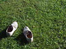 Trainers abandoned on the grass. The trainers abandoned on the grass, concept of summer activities, outdoor copy space shot royalty free stock photos
