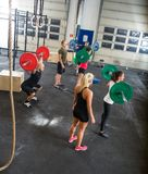Trainers And Athletes In Weightlifting Class. High angle view of crossfit trainers and athletes in weightlifting class at gym stock photography