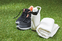 Trainers with bottle of water and towel on green pitch. Close up of trainers with bottle of water and towel on green pitch Royalty Free Stock Photo