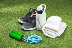 Trainers with bottle of water and towel with skipping rope on grass. Close up of trainers with bottle of water and towel with skipping rope on grass Royalty Free Stock Photography