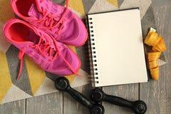 Trainers, dumbbells, ribbon, mat on floor. Stock Image