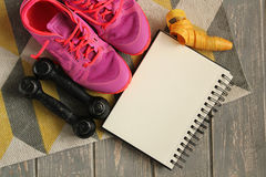 Trainers, dumbbells, ribbon, mat on floor. Royalty Free Stock Image