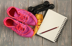Trainers, dumbbells, ribbon, mat on floor. Royalty Free Stock Images