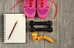 Trainers, dumbbells, ribbon, mat on floor. Stock Photos