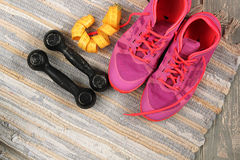 Trainers, dumbbells, ribbon, mat on floor. Stock Photo