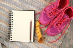 Trainers, dumbbells, ribbon, mat on floor. Stock Photos