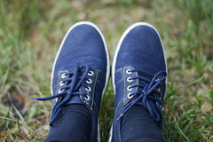 Trainers on the grass. Legs are on the rest after a long walk Royalty Free Stock Images