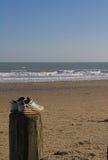 Trainers on groyne overlooking sea Stock Photography