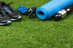 Trainers, jump rope, dumbbells with bottle and mat. On grass Stock Images