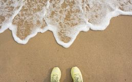 Trainers meeting wave. Green sport trainers on the beach and sea wave Stock Images