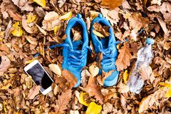 Trainers and smartphone on colorful leaves on the ground. Blue trainers, smartphone and water bottle on colorful leaves on the ground. Autumn nature Royalty Free Stock Image
