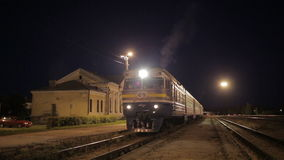 Traing leaving small rural station. Passenger train leaving small rural station at night stock video footage