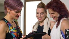 Trainieren Sie die Frau, die mit sportlichen Frauen über Wellness unter Verwendung des Tabletten-PC-Gerätes an der Trainingsklass stock footage