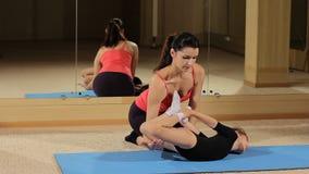 Trainieren Sie, um Rückenmuskulatur zu verstärken Ausbildende schöne gelockte Mädchen Helfende Übung des Gymnastiktrainers Anleit stock video
