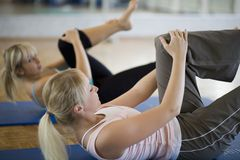 Training. Blonde women train her abdominals Royalty Free Stock Photos