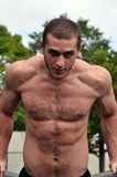 Training. This is a picture of a young man standing at a dip station while bending his elbows. He is shirtless and facing the camera Stock Photo