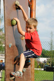 Training. Young boy climbing a training wall, looking to the camera Royalty Free Stock Images