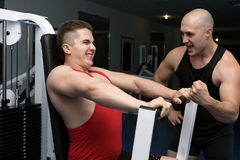 Training. Two young guys go in for sports in a gym Royalty Free Stock Photography