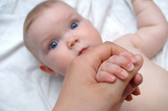 Training. Mother massaging hands of her baby Stock Photos
