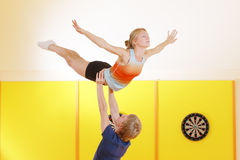 Training acrobatic feat. Young couple training acrobatic feat in gym Stock Photography