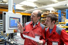 Training and apprenticeship in industry. Talk at the cnc machine stock photo