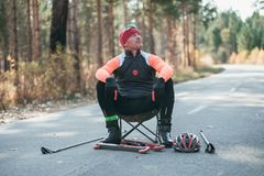 Training an athlete on the roller skaters. Biathlon ride on the roller skis with ski poles, in the helmet. Athlete is royalty free stock images