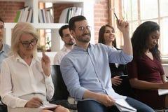 Training audience participants raise hands to ask question at workshop