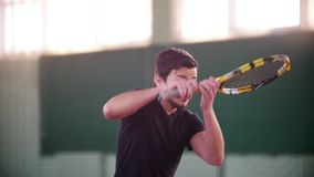Training auf dem Tennisplatz Der junge Mann, der zum Spiel aber zu ihm fertig wird, erhält durch Tennisbälle zerstreut bedeckung stock video footage