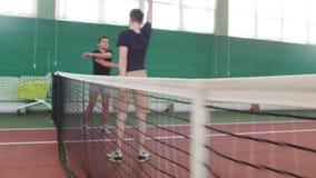 Training auf dem Tennisplatz Junge Männer, die vor dem Spiel aufwärmen Das Gitter im Fokus und in einem Wagen gefüllt mit Tennis stock video footage
