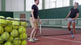 Training auf dem Tennisplatz Junge Männer, die vor dem Spiel aufwärmen Ein Wagen gefüllt mit Tennisbällen stock video footage