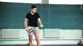 Training auf dem Tennisplatz Junger Mann, der den Ball betrachtet und dann ihn mit einem Schläger schlägt stock video