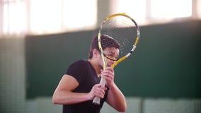 Training auf dem Tennisplatz Junger Mann erhält durch Tennisbälle zerstreut Abdeckung mit einem raquet stock footage