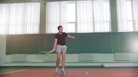Training auf dem Tennisplatz Junger Mann wirft Schläge der Ball mit einem Schläger stock video
