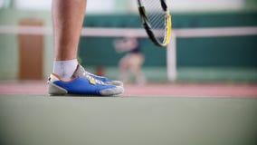 Training auf dem Tennisplatz Zwei junge Männer, die Tennis spielen Füße in den blauen Stiefeln im Fokus stock video footage