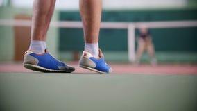 Training auf dem Tennisplatz Zwei junge Männer, die Tennis spielen Füße im Fokus stock footage