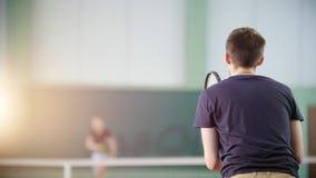 Training auf dem Tennisplatz Zwei junge Männer, die Tennis spielen Schlagen des Balls mit einem Schläger Rückseitige Ansicht stock video footage